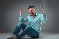 Handsome young man sitting on a floor with raised hands gesturing happiness on gray background Royalty Free Stock Images