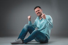 Handsome young man sitting on a floor with raised hands gesturing happiness on gray background Royalty Free Stock Photos