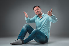 Handsome young man sitting on a floor with raised hands gesturing happiness on gray background Stock Images