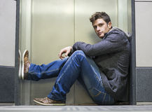 Handsome young man sitting in front of elevator doors Stock Images