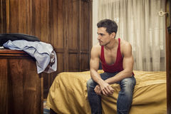 Handsome young man sitting on his bed Stock Images
