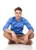 Handsome young man sitting with his legs crossed. On isolated background Royalty Free Stock Images