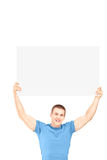 Handsome young man sitting and holding a white panel. Above his head isolated on white background Stock Images