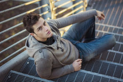 Handsome young man, sitting and leaning on metal Royalty Free Stock Image