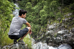 Handsome young man sitting in lush green mountain. Handsome muscular young man sitting in lush green mountain scenery looking down at water stream Royalty Free Stock Image