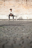 Handsome young man sitting on marble bench with bricks background Stock Photo