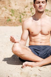Handsome young man sitting and meditating on the beach Stock Image