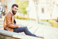 Handsome young man sitting next to his laptop on the stairs while talking on his phone Stock Images