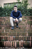 Handsome young man sitting outdoor on old brick stairs Stock Images