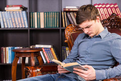 Handsome young man sitting reading Royalty Free Stock Photos