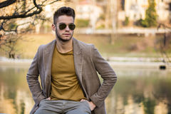 Handsome young man sitting by river in city Royalty Free Stock Photos