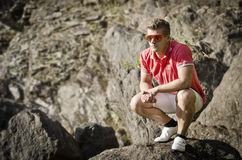Handsome young man sitting on rock Royalty Free Stock Photo