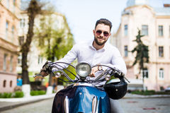 Handsome young man while sitting on scooter Stock Photos