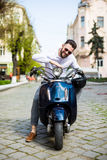 Handsome young man while sitting on scooter Royalty Free Stock Image