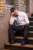 Handsome young man sitting on stairs. Stock Photo