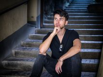 Handsome young man sitting in European city alley. Handsome young man sitting on steps in European city street, leaning on his knee, looking away, daydreaming Royalty Free Stock Photos