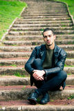 Handsome young man sitting on steps outdoors. Royalty Free Stock Photos