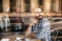 Handsome young man sitting at table in cafe, view from outdoors. Through window royalty free stock photos