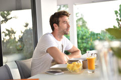 Handsome young man sitting at the table having breakfast Stock Photos
