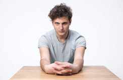 Handsome young man sitting at the table Stock Images