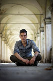 Handsome young man sitting under old colonnade Stock Photo