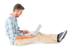 Handsome young man sitting using laptop Stock Image