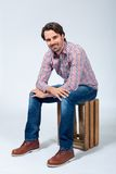 Handsome young man sitting on a wooden box Royalty Free Stock Images
