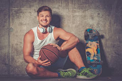 Handsome young man with skateboard outdoors Stock Images