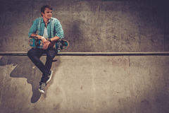 Handsome young man with skateboard outdoors stock photography