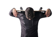 Handsome young man with skateboard over his shoulders. Handsome trendy young man with skateboard over his shoulders, resting his arms, isolated on white Stock Photography