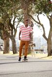 Handsome young man skateboarding outdoors in park Stock Photography