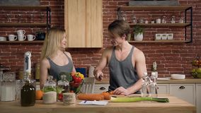 Handsome young man slicing carrot on wooden cutting board while coming his girlfriend with plate of vegetable. stock footage