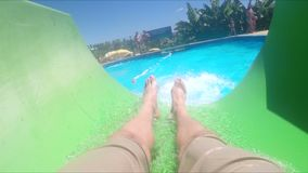 Handsome young man sliding down water slide. In aquapark or water amusement park, having a good time in a sunny summer day stock video footage