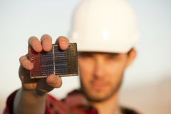 Handsome young man with small solar panel. Handsome young man wearing hardhat with small solar panel in hand Royalty Free Stock Photos