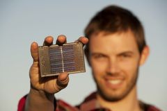 Handsome young man with small solar panel. In hand Royalty Free Stock Images