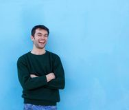 Handsome young man smiling against blue background Royalty Free Stock Photo