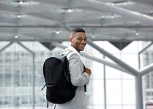 Handsome young man smiling with bag at airport Stock Images