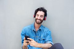 Handsome young man smiling with cellphone and headphones Royalty Free Stock Image