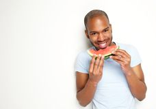 Handsome young man smiling and eating fresh watermelon Stock Photos