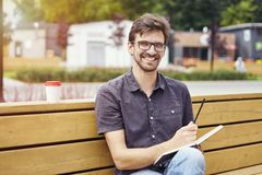 Handsome young man smiling face writing in a note book sitting outside. Guy wearing glasses alone working. Concept of education. Students youth Stock Photography