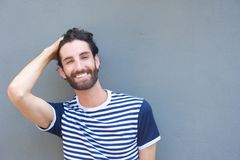 Handsome young man smiling with hand in hair Stock Photography