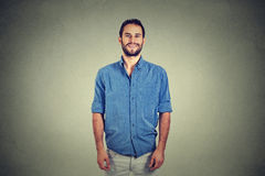 Handsome young man smiling isolated against gray wall background stock photography