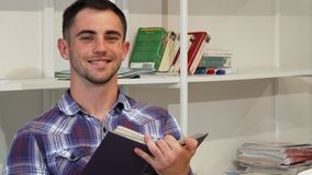 Handsome young man smiling joyfully while reading a book royalty free stock photo