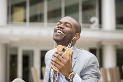 Handsome young man smiling while listening to music stock image
