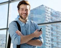 Handsome young man smiling with mobile phone Stock Photo