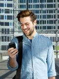Handsome young man smiling with mobile phone at station Stock Images