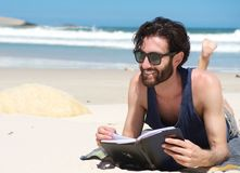 Handsome young man smiling and reading book on the beach Royalty Free Stock Images