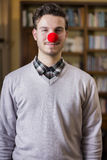 Handsome young man smiling with red clown nose. Standing in a living room Stock Photo