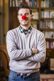 Handsome young man smiling with red clown nose. Standing in a living room Royalty Free Stock Image