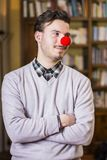 Handsome young man smiling with red clown nose. Standing in a living room Stock Images